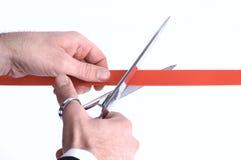 het snijden van een rood lint met schaar Royalty-vrije Stock Afbeelding