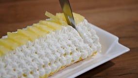 Het snijden van een stuk van de cake van het ananasbroodje stock video