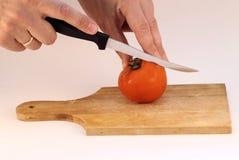 Het snijden van een tomaat stock afbeelding