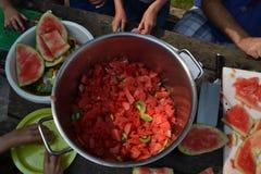 Het snijden van een watermeloen in stukken stock foto's