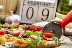 Het snijden van gebakken pizza op de achtergrond met kalender Stock Foto's