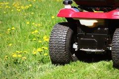 Het snijden van het gras van op een tractorgrasmaaimachine stock foto