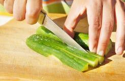 Het snijden van komkommer voor salade Royalty-vrije Stock Afbeeldingen