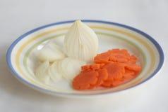 Het snijden van uien en wortel op een plaat 3 Stock Foto's