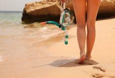 Het Snorkelende Masker van de vrouwenholding dichtbij haar Benen op het Strand Stock Afbeelding