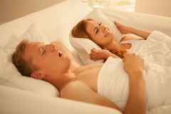 Het snurken man en boze vrouw stock afbeeldingen