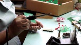 Het soldeerselcomponenten van vrouwenhanden stock video