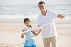 Het Spaanse meisje en papa spelen met stuk speelgoed op strand royalty-vrije stock foto's