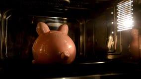 Het spaarvarken bakt in de microgolf Steunend geld, geld die aan toestellen besteden stock footage