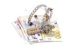 Het spaarvarken padlocked met kettingen en hangslot op euro bankbiljetten stock foto's