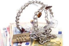 Het spaarvarken padlocked met kettingen en hangslot op euro bankbiljetten royalty-vrije stock afbeeldingen