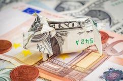 Het spaarvarken van de dollarorigami op euro en dollarbankbiljetten Stock Foto's