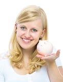 Het spaarvarken van de vrouwenholding Stock Foto