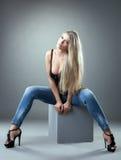 Het spectaculaire blonde stellen op kubus in studio royalty-vrije stock foto's