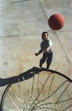 Het speelbasketbal van de jongen Stock Foto's