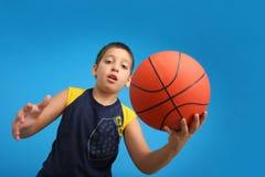Het speelbasketbal van de jongen. Blauwe achtergrond stock foto