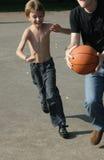 Het speelbasketbal van de mens en van de jongen stock fotografie