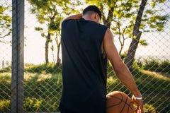 Het speelbasketbal van de mens Sportcompetities, spel, Mens met bal op basketbalhof, gelukkig gezicht, aantrekkelijke lach, fitne Stock Foto's