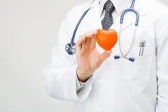 Het speelgoed-hart van de artsenholding in zijn hand Stock Afbeeldingen
