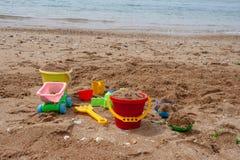 Het speelgoed van heldere plastic kinderen in het zand Concept strandrecreatie voor kinderen stock afbeeldingen