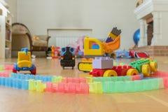 Het speelgoed van kinderen op de vloer Close-up Het graafwerktuig, de trein en de auto van kinderen De kinderen verlaten achter k stock fotografie