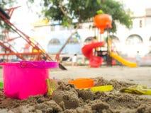Het speelgoed voor zand die het heeft een mooie kleur op het zand leggen graven de achtergrond is een speelplaats Stock Foto's