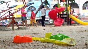 Het speelgoed voor zand die het heeft een mooie kleur op het zand leggen graven de achtergrond is een speelplaats heb kinderen en stock footage