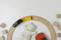Het speelgoedkader met teddy, rode auto, de houten kubussen en het stuk speelgoed leiden op de witte achtergrond op Stock Foto
