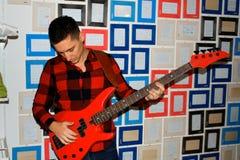 Het speellied van de gitaarspeler binnen Stock Foto's
