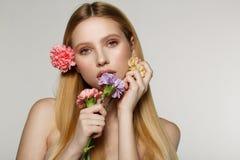 Het speelse en sexy portret van vrij vrolijke vrouw met de lente bloeit dichtbij haar gezicht stock foto