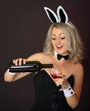 Het speelse meisje bij de partij giet wijn Stock Foto
