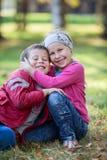 Het speelse meisje en de jongen in de herfstpark, sluiten omhoog Stock Foto