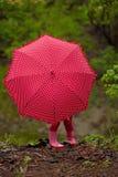 Het speelse meisje verbergen achter kleurrijke paraplu in openlucht Royalty-vrije Stock Afbeeldingen