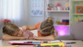 Het speelse vrouwelijke kind het schilderen gezicht van slaapbroers, familiegrap, voor de gek houdt dag stock video