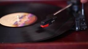 Het speelt een vinylplatenspeler, een retro platenspeler, een oude muziekspeler stock footage