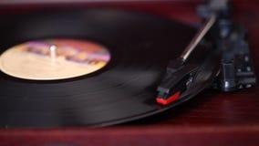 Het speelt een vinylplatenspeler, een retro platenspeler, een oude muziekspeler stock videobeelden