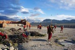 Het speelvolleyball van beginnersgompa tijdens de vakantie, in de rug van het klooster, op de achtergrond van het Himalayagebergt Stock Afbeelding