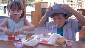 Het spel met voedsel, gelukkige kinderenvrienden heeft pret met Frieten en maakt grappige gezichten in Straatkoffie stock videobeelden