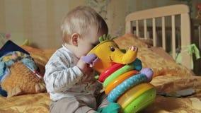 Het spel van de babyjongen met hem speelgoed stock footage