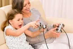 Het spel van de het spelcomputer van de grootmoeder en van de kleindochter Stock Foto
