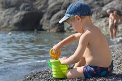 Het spel van de jongen op het strand Stock Afbeelding