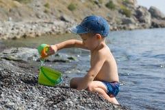 Het spel van de jongen op het strand Royalty-vrije Stock Afbeeldingen