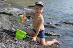 Het spel van de jongen op het strand Stock Afbeeldingen