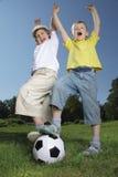 Het spel van de jongen in voetbal Stock Afbeeldingen
