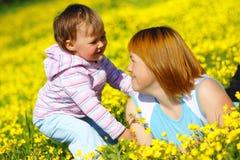 Het spel van de moeder en van het kind op weide Stock Fotografie