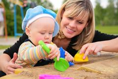 Het spel van de moeder en van het kind in zandbak Royalty-vrije Stock Foto's