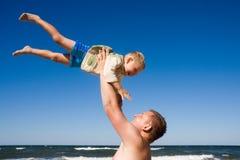 Het spel van de vader met zoon op strand Stock Afbeeldingen