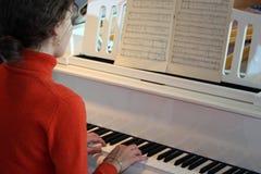 Het spel van de vrouw op piano stock foto