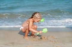 Het spel van het babymeisje op het strand. Stock Fotografie