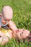 Het spel van het mamma en van de baby op het gras stock foto